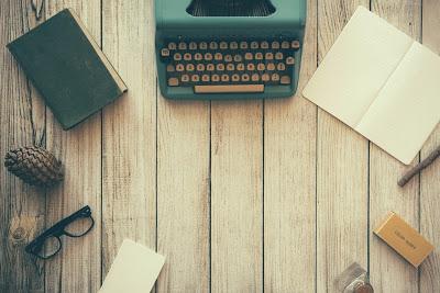 blat zbity z desek, na którym w okręgu leżą przedmioty takie jak: maszyna do pisania, notes, książka, okulary, przybory do pisania