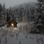 domek na pokrytej śniegiem polanie. W okienku pali się światło. W tle zaśnieżone sosny.