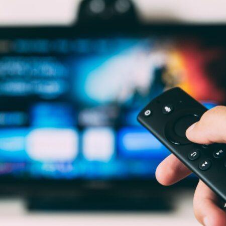 Pilot w dłoni na tle telewizora